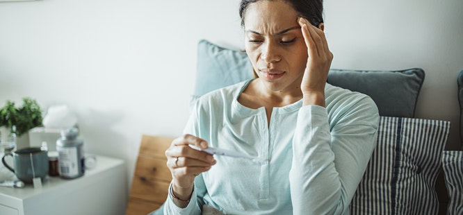 woman with headache feeling sick taking her temperature wonders if she has been exposed to covid-19