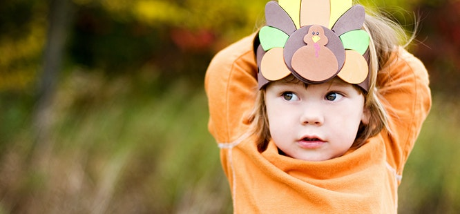 child in orange shirt wearing turkey hat craft at thanksgiving in covid