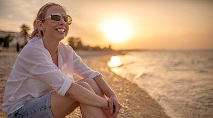 woman wearing sunglasses at the beach and sunscreen following dermatologist advice