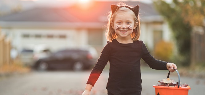 girl dressed as black cat for halloween with candy basket
