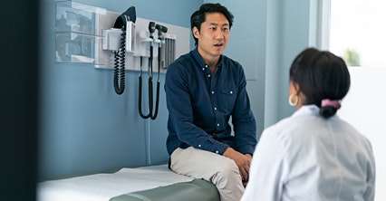 man in blue shirt comfortable talking with his primary care doctor at medhelp