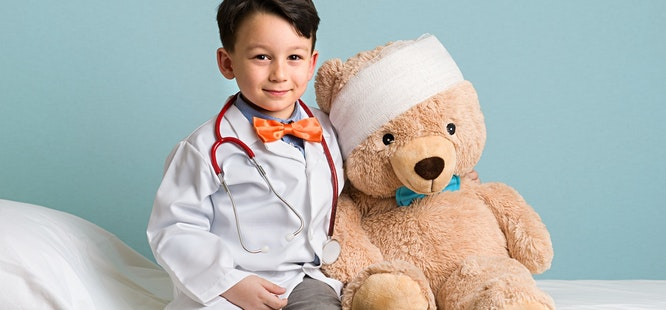 little boy wearing stethoscope and lab coat pretending to be a primary care doctor