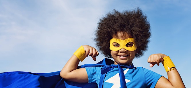 boy wearing superhero costume with cape and mask