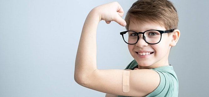 Child wearing glasses showing arm after vaccine