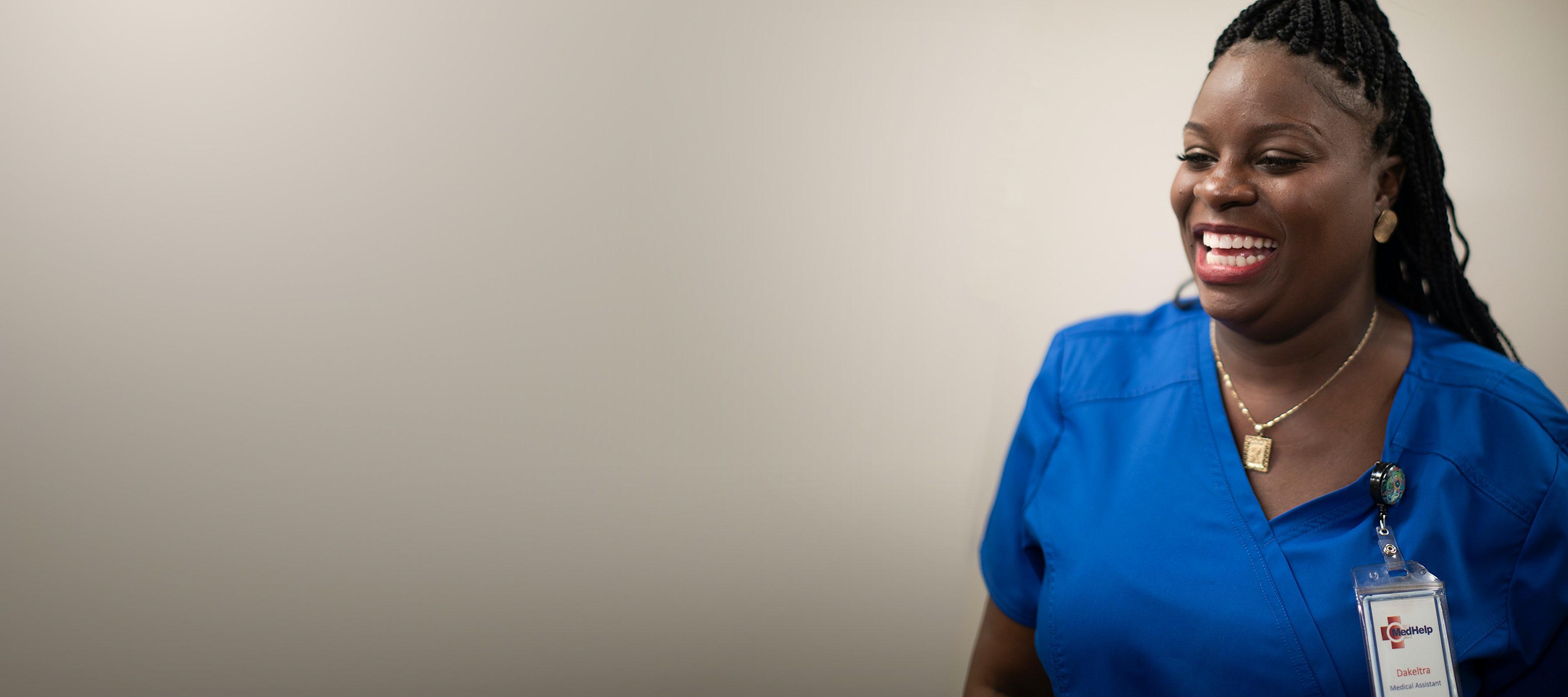 smiling nurse in blue scrubs at medhelp birmingham urgent care clinic