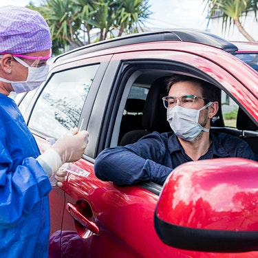 man in red car wearing mask receiving rapid covid test from nurse in blue protective gown