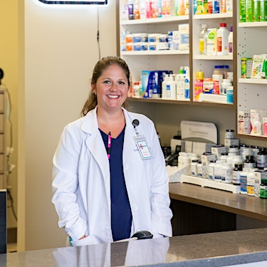 female pharmacist smiling at medhelp 280 urgent care primary care independent pharmacy