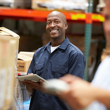 smiling man working at warehouse receiving occupational health services