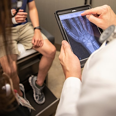 doctor reading digital hand xray on ipad while patient sits on exam table with arm cast