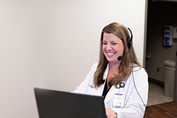 nurse practitioner wearing headset providing online telehealth virtual doctor visit