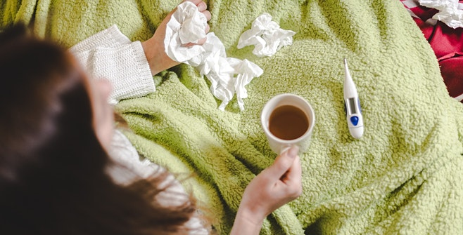 woman with respiratory illness in bed with tissues deciding to go to urgent care